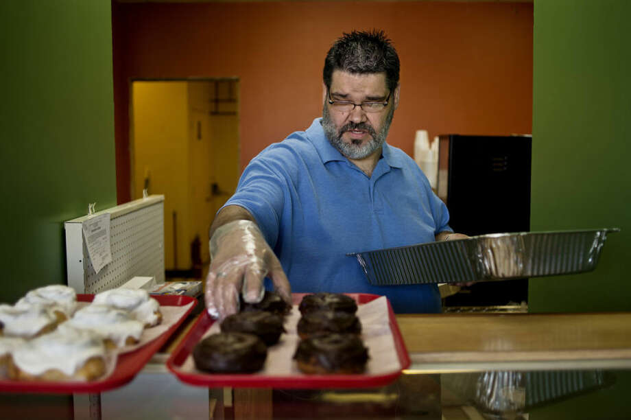 Christopher Williams sets doughnuts out on a tray Monday afternoon during Timbers Bistro and Bakery's soft opening  in Eastlawn Plaza on South Saginaw Road. Photo: SEAN PROCTOR | Sproctor@mdn.net