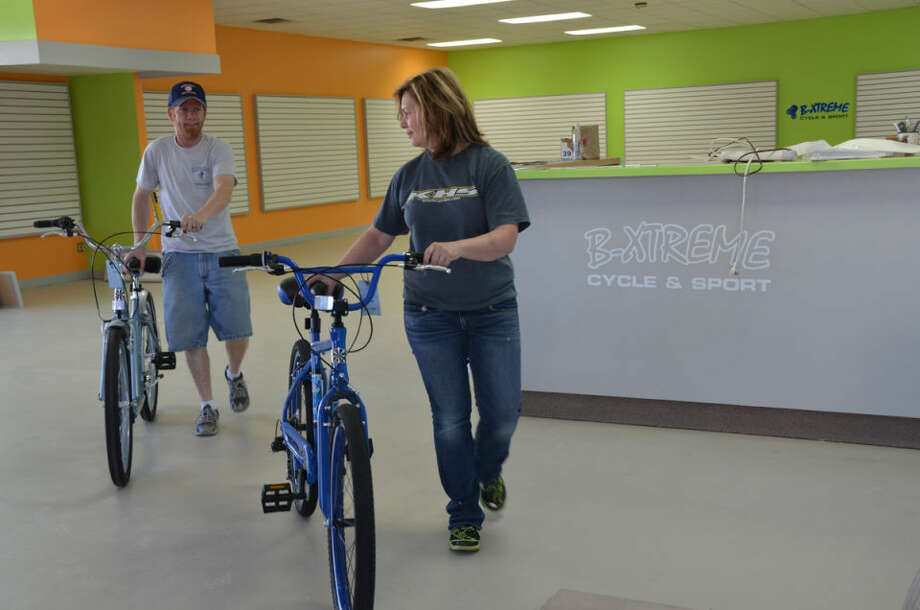 Husband and wife owners Todd and Julia Atkinson wheel in new bikes as they neared the grand opening of their new location for B Xtreme Cycle & Sport on Rodd Street. Photo: TRACY BURTON   For The Daily News