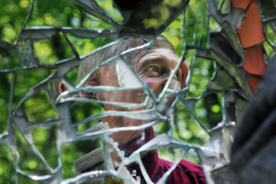 """Reid Calcott, of Saginaw, looks at mirror shards cemented onto the side of the John Pratt Mosaic House. The house is the creation of John Pratt, a schizophrenic artist who used the mosaic process as a form of healing. """"If you look at yourself in the mirrors you can view yourself as a schizophrenic would,"""" says Linda Smith, founder of Creative 360, """"John viewed his life as a broken mirror, and the house allowed him to put the pieces back together."""" Photo: Zack Wittman"""