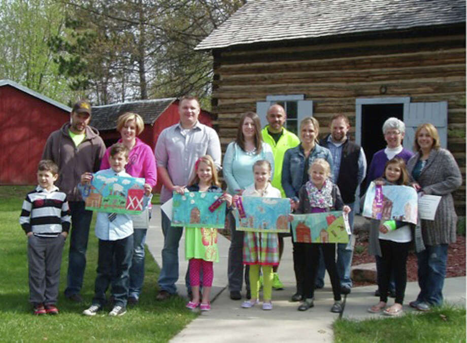 Standing in front of the Smith Log Cabin at the Sanford Centennial Museum are second grade Sanford Meridian Elementary students who are the winners from more than 70 entries of the 2014 Early Pioneer Log Cabin Day Art Contest. Pictured from left holding their winning pictures with parents behind are Cooper Seidl (brother), Andrew Seidl (first place) parents Tom and Krissy, Kaylee Riggie (second place), Jordyn Riggie (honorable mention) parents Jake and Dana, Josie Barriger (third place) parents Rod and Carrie, Matika Grice (honorable mention) parents Holly (far right) and Mark (not pictured). Art teacher Candee Mashue and second grade teacher Bob Blades are in the back row.