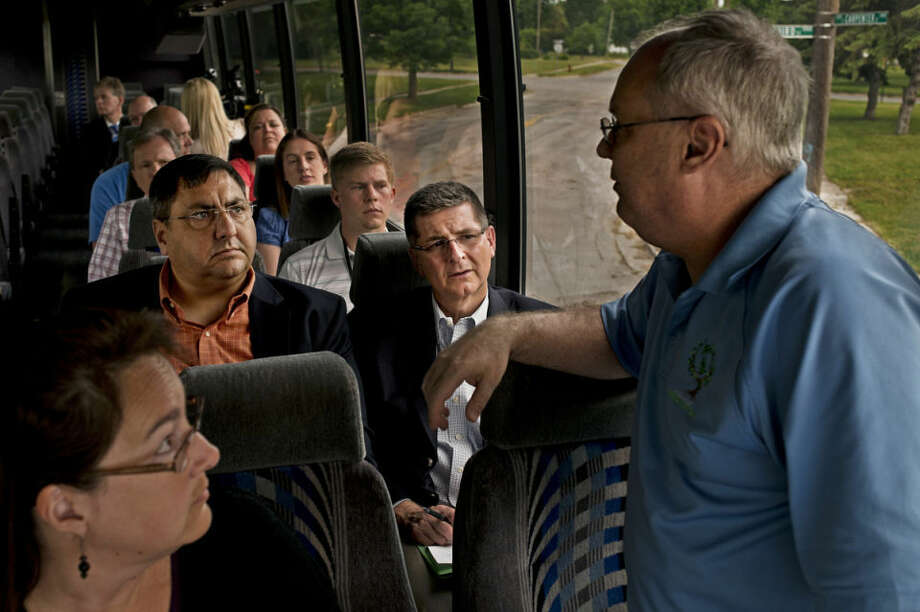 Dan Wyant, Director of the Michigan Department of Environmental Quality, center, and State Representative Jim Stamas, right, listen to Steve Lucas, Associate EH&S Remediation Director at Dow Chemical during a bus tour on Friday morning. The tour took Wyant through active cleanup sites in the Dow Chemical Soil Remdiation Project as well as Stadium District West, a brownfield redevelopment area. Photo: Sean Proctor