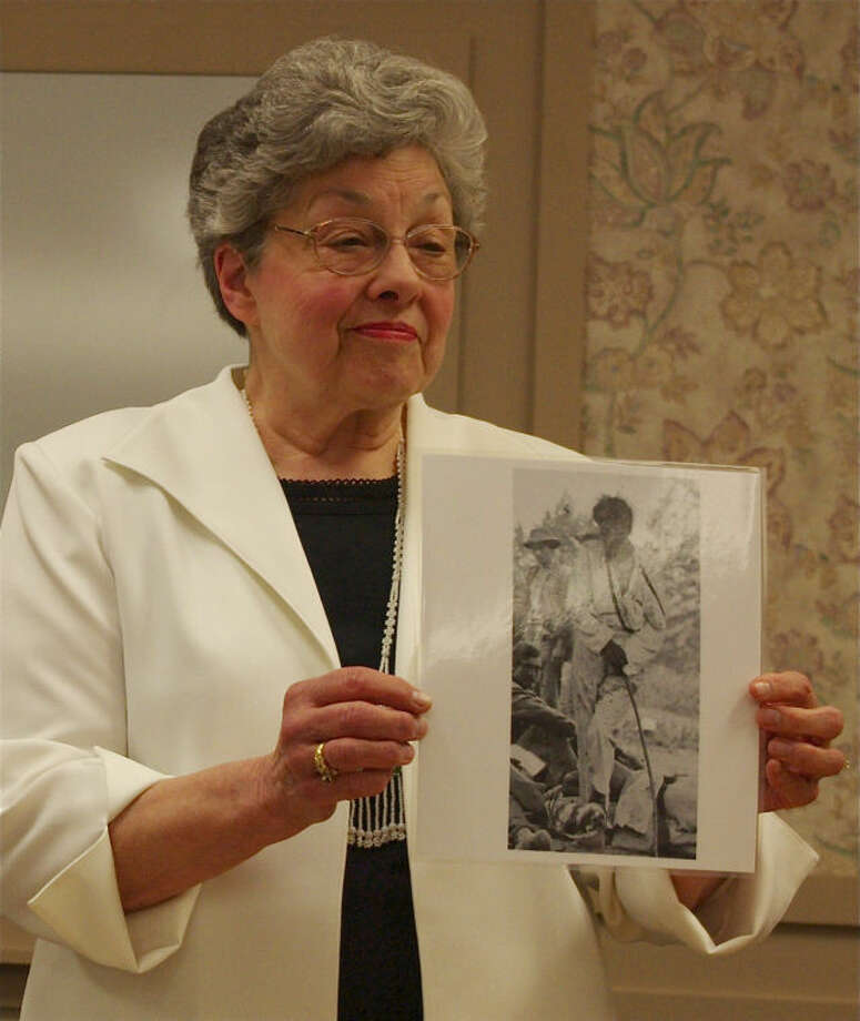 Quita Shier of Larkin Township shows Midland County senior citizens a photograph believed to be of former Saginaw County resident Thomas Kechittigo. She said the photograph was taken soon after the 1864 Battle of Spotsylvania, in which Sgt. Kechittigo was shot in the left forearm. Photo: STUART FROHM  | For The Daily News