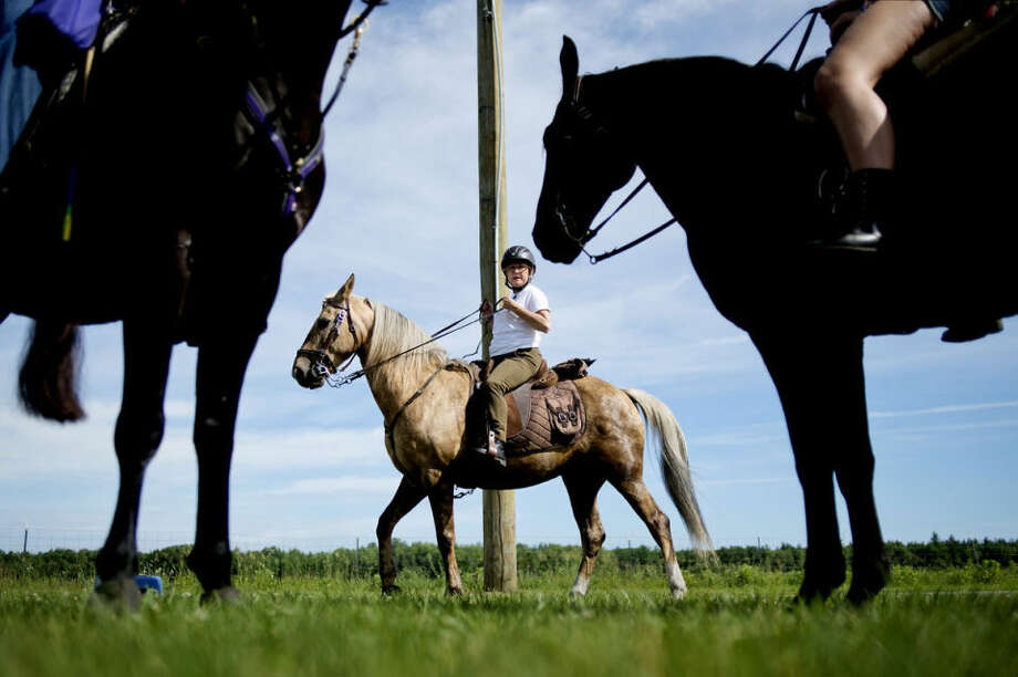 Vicki Winschester, center, and other riders ready their Tennessee Walker horses before leading a group on a two-hour trail ride from the Midland County Fairgrounds to Midland City Forest Saturday during the Saddle up for St. Jude event. Photo: NICK KING | Nking@mdn.net