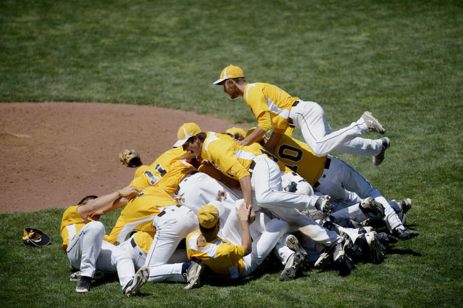 Bay City Western's David Fegan soars over a pile of players after the Warriors cliched the state championship in the game against Grosse Pointe South at Michigan State University in East Lansing on Saturday. Photo: NEIL BLAKE | Nblake@mdn.net