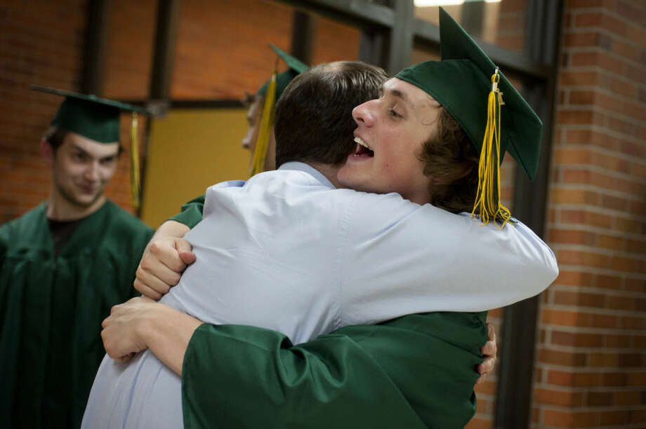 English teacher Andrew Fry hugs and congratulates senior Lance Harmer as the students make their way into the gymnasium for the 2014 H.H. Dow High School commencement ceremony Friday June 6. Photo: Taryn Wattles | For The Daily News