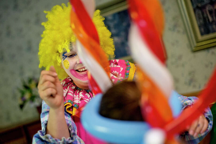 Giggles the clown smiles after placing a balloon hat she made on the head of Brooklyn Duranceau, 9, during a carnival Wednesday at Brittany Manor. Photo: Nick King/Midland  Daily News / Midland Daily News