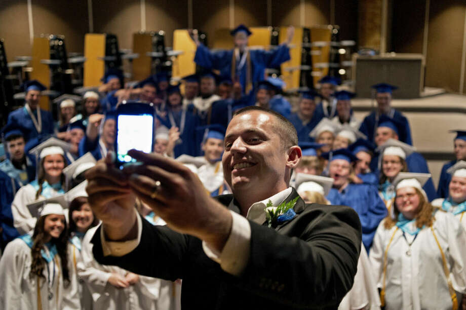 SEAN PROCTOR | sproctor@mdn.netDoug Cellini, a science teacher and the master of ceremonies at Coleman High School's graduation event, takes a picture of himself with the graduating class in the background on Sunday. Photo: Sean Proctor