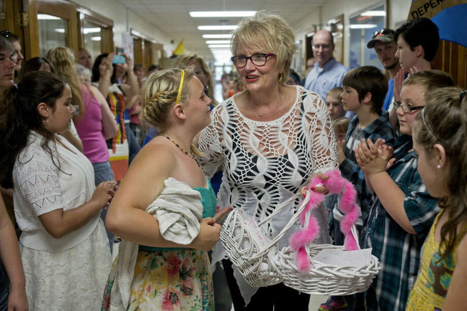 "Bonnie Westervelt, the principal at Eastlawn Elementary School, walks down the hallway as staff, students and parents show their appreciation by cheering and handing her cards and flowers on the last day of school. Westervelt, who has been at Eastlawn for four years, is retiring from education and shifting to retail. ""I can say goodbye to anybody, but those kids' that's the hardest,"" Westervelt said. Throughout the week, the school honored her in various ways. On Monday, they wore red lipstick, on Tuesday, they wore leopard print, and Wednesday was ""Harley-Davidson Day,"" each a surprise to Westervelt. ""I've been holding it together pretty good until today,"" she said. Photo: SEAN PROCTOR 