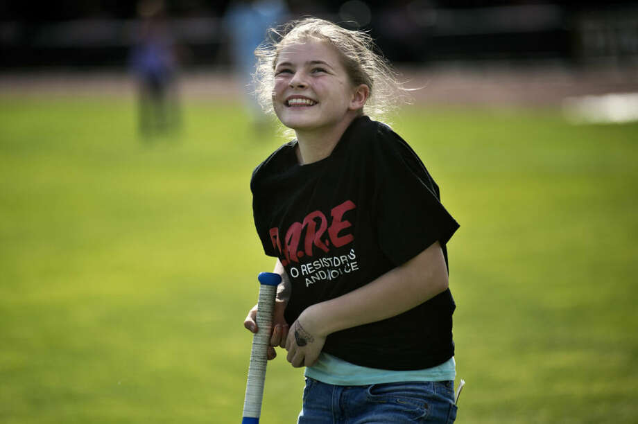 Taylor Hendrickson, 11, of Midland, laughs after missing a pitch during a game on Friday during the Midland Project D.A.R.E. Graduation at Dow Diamond. The 10-week course helps to teach fifth graders good coping skills, how to pick good friends and resist and avoid poor choices and situations, according to School Resource Officer Jai Mahabir. Midland Police Chief Clifford Block and Midland County Sheriff Scott Stephenson spoke to the graduates. Photo: Sean Proctor/Midland Daily News