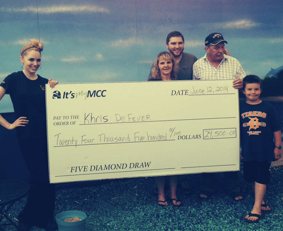 Khris DeFever, center, stands behind a large check with her son Max, husband Don, grandson Cameron, and an employee at The Creek Grill. Photo: Photo Provided