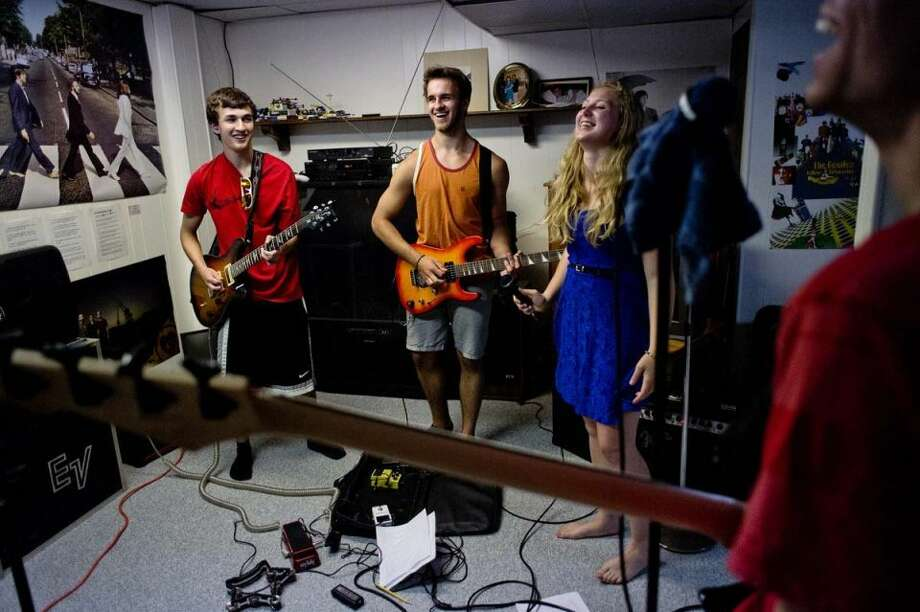 Members of the band Loose Change, from left, Tristayn Owen, 16, Jimmy Bergmooser, Abbey Drumright and Nick Shahin, all 18, practice on Tuesday in the basement of Shahin's home. Not pictured is band drummer Elliott Miller. The group, made up of Midland teens, will be performing at Tunes by the Tridge on Thursday, June 26 at 7p.m. Photo: Nick King/Midland  Daily News
