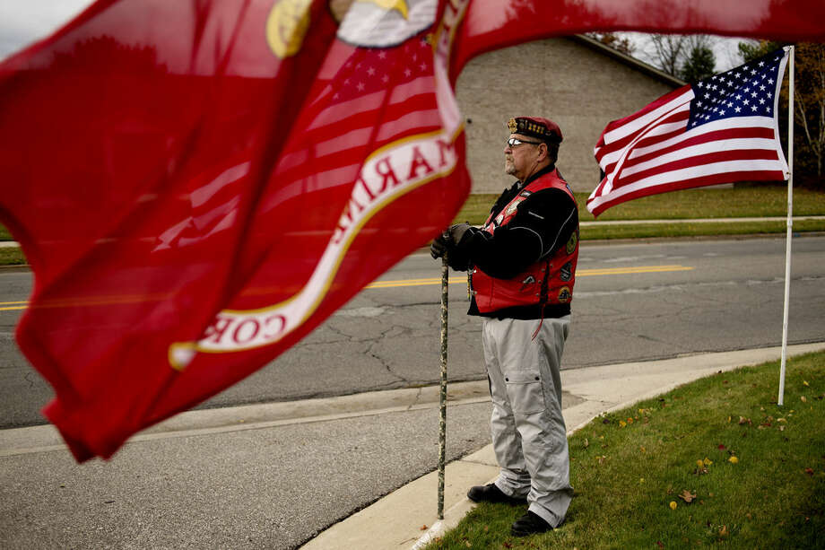 """Patroit Guard Riders member Bill Schwalm of Saginaw Township holds a flag at the entrance to The Smith Miner Funeral Home as family and friends of Lance Cpl. Steven Szymanski arrive before his funeral on Wednesday. """"It's an honor to be here,"""" Schwalm said. Photo: NEIL BLAKE   Nblake@mdn.net"""