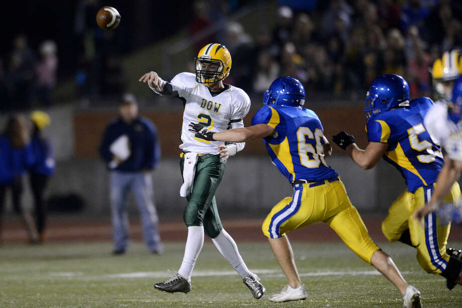 Dow High's Alec Marty, left, throws a pass in last week's game against the Midland High Chemics. Photo: NICK KING | Nking@mdn.net
