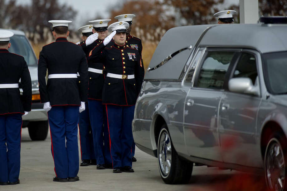 Marine honor guard members salute the hearse carrying the body of Lance Cpl. Steven Szymanski on Monday outside the Smith-Miner Funeral Home in Midland.