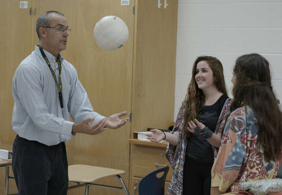 Dow High teacher Thomas McNamara, left, uses a volleyball and motion sensor to map the kinematics of tossing the ball into the air as students Ellen Lavigne, center, and Stephanie Carras, right, observe. A similar process is used to map the kinematics of the solar cars. Photo: Photo Provided