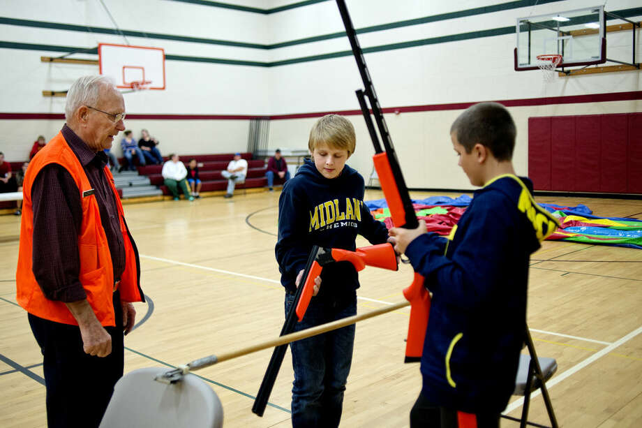 Safety instructor Ken Johnson, left, watches as Macklan Gay, center, and Josh Barriger, right, practice the safe way to cross a fence when hunting during a Michigan hunter safety class at the North Midland Family Center. The youths were using using practice shotguns. Photo: NICK KING | Nking@mdn.net