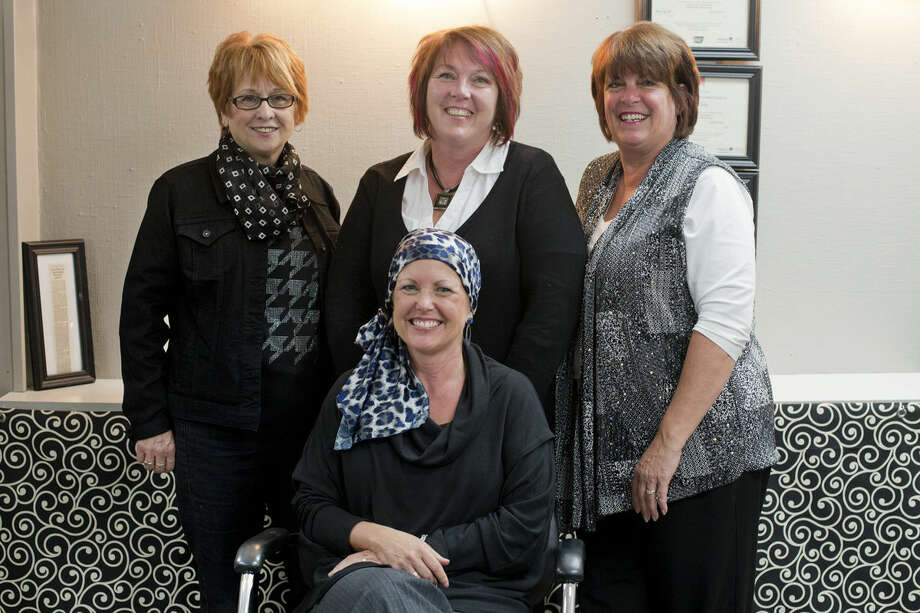 Ann Szymanowski, seated, smiles for a photo with Betty Gaffke, from left, Cindy Parsons and Sandy Groulx, all cosmetologists with the Mane Hair Company in Midland. Szymanowski went through the Look Good Feel Better program in June with the stylists. The program was created to serve people with cancer by giving them beauty products and advice to help combat the side effects of cancer treatments. Photo: Neil Blake/Midland Daily News