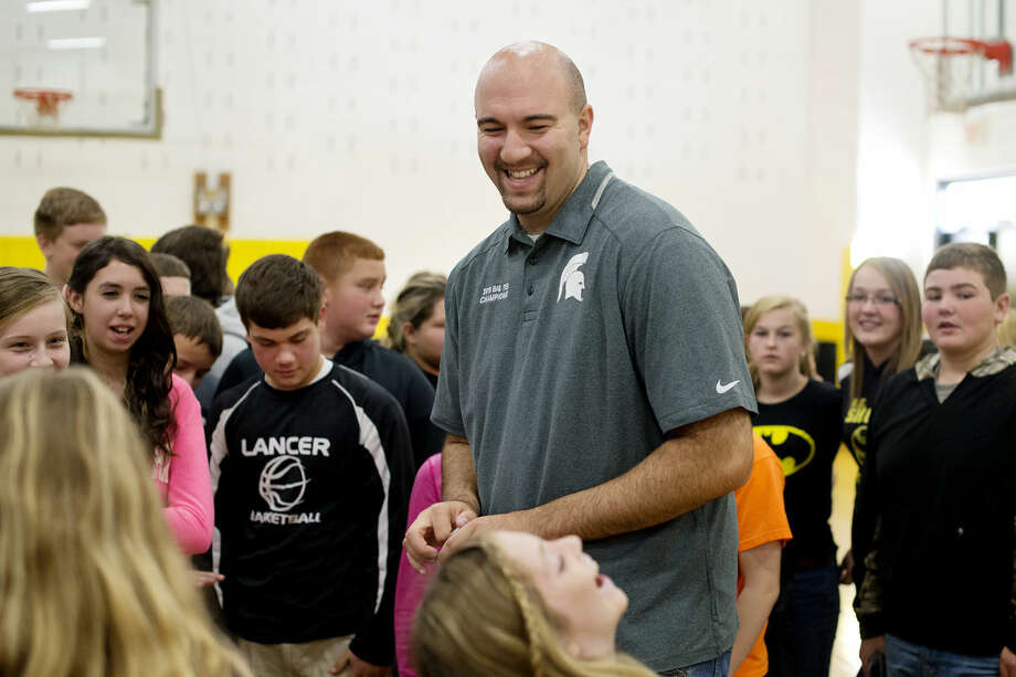 Anthony Ianni, a former basketball player for Michigan State University, laughs as seventh-grader Kaitlyn Ososki tries to remember his Twitter handle after he gave an anti-bullying message to the student body at Bullock Creek Middle School on Wednesday. Photo: NEIL BLAKE | Nblake@mdn.net