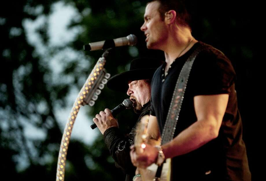 Eddie Montgomery, left, and band mate Troy Gentry perfomr during the Montgomery Gentry concert Sunday at Chippewassee Park. Photo: NICK KING | Nking@mdn.net