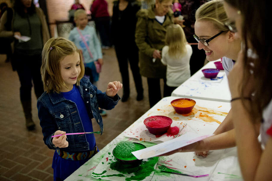 Kaya Vrable, 7, left, looks at the design made by soap bubbles and paint on a piece of paper held by Kettering University student Alysia Walczak, center, at the STEM activities booth before the American Girl Fashion Show on Sunday at the Midland Center for the Arts. Fellow schoolmate Erin Kissick, right, looks on. The experiment was to show surfactants in action. The STEM activities were run by the Women Chemists Committee of the Midland Chapter of the American Chemical Society. Photo: NICK KING | Nking@mdn.net