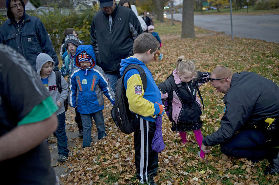 Midland Police Officer Andrew Hawkins, right, helps Allie DeHaan, a kindergartener, slip her shoe back on as her brother, Jeff DeHaan, a fourth-grader at Eastlawn Elementary School, looks on during Walk to School Day on Wednesday morning. Photo: SEAN PROCTOR | Sproctor@mdn.net