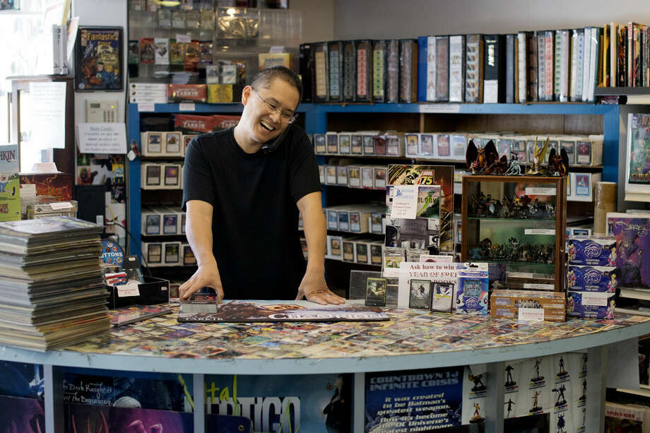 Andrew Iwamasa talks to a customer on the phone at Collector's Corner in Midland. Iwamasa has run the store, which specializes in comic books, cards and games, for the past 20 years. Photo: NEIL BLAKE | Nblake@mdn.net