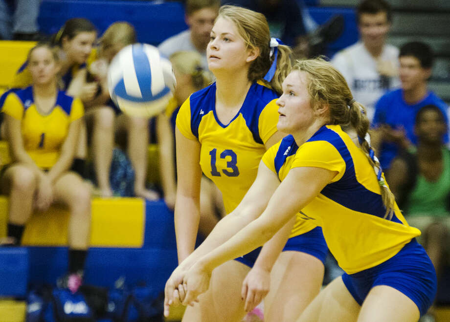 Midland's Kailey Warner, right, bumps the ball during a volleyball match against Bay City Western at Midland High School on Tuesday. The Chemics won in three games. Photo: DANIELLE MCGREW   For The Daily News