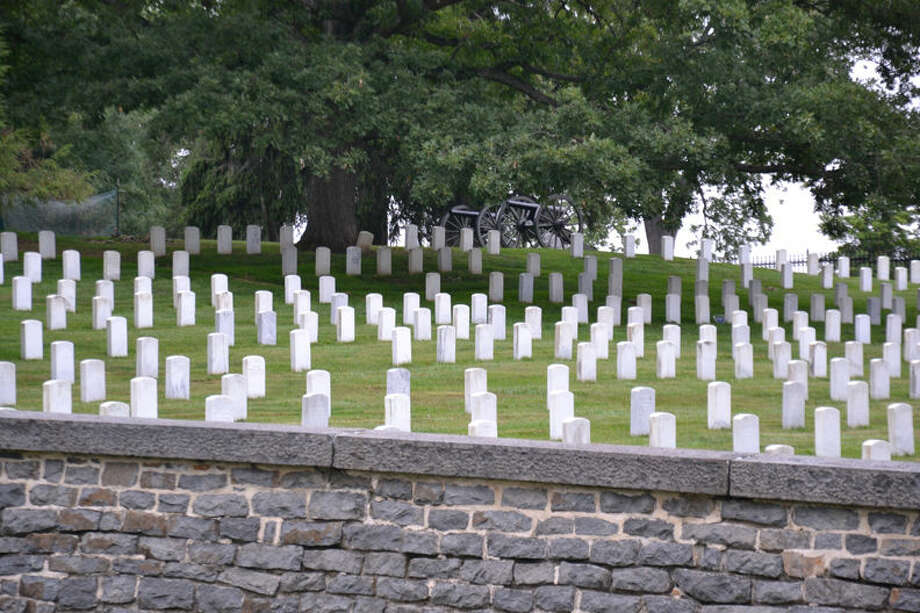 """One of the post-World War II sections on the south side of the cemetery. Most of the burials in this section World War II-era and Korean Conflict. The guns here are Civil War, meant to mark the positions of Union batteries during the Battle of Gettysburg, July 1-3, 1863. The stone wall was constructed around the cemetery between 1866-1869. The large tree is an 1890's planting; only one tree in the cemetery is a """"witness tree,"""" a honey locust just to the right of this view and out of frame. Photo: Photo By Steve Griffin"""
