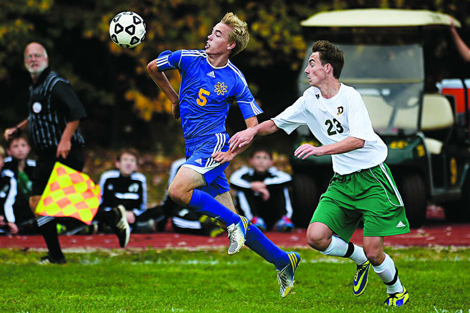 Midland's Ryan Swierzbin tries to knock the ball down against Dow's Jake Davidson Wednesday during their game at Dow High School. The Chemics beat the Chargers 1-0. Photo: SEAN PROCTOR   Sproctor@mdn.net