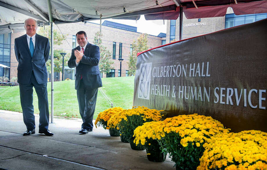Former SVSU President Eric Gilbertson, left, looks on as Jeff Martin, chair of the SVSU Board of Control, unveils the temporary sign to mark Gilbertson Hall. Photo: Photo Provided