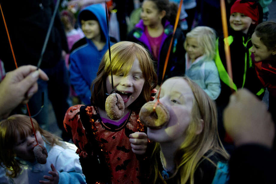 Cousins Ailah Elwell, left, and Josie Nelson, both 8 and from Midland, participate in the donut eating contest on Thursday during the annual Downtown Midland Pumpkin Festival on Main Street in downtown Midland. Comerica Bank and Johnson's Giant Pumpkin Farm sponsored the contest, where participants had to eat donuts off strings without using their hands. Photo: NICK KING | Nking@mdn.net