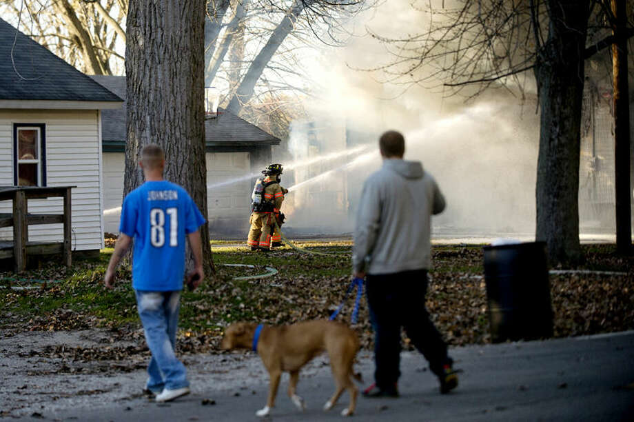 Neighbors look on as Midland City firefighters battle a blaze Saturday at a house on Sandow Road, just north of M20. Photo: Nick King Midland Daily News