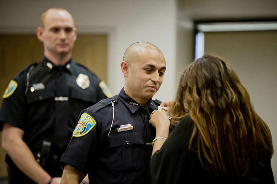 Brian Soule holds still as his mother, Theresa Soule, pins on his new badge, number 158, on his uniform during his swearing-in ceremony as a Midland Police Department officer. Soule graduated from the Delta College Police Academy and worked at the Flint Police Department. Photo: NEIL BLAKE   Nblake@mdn.net