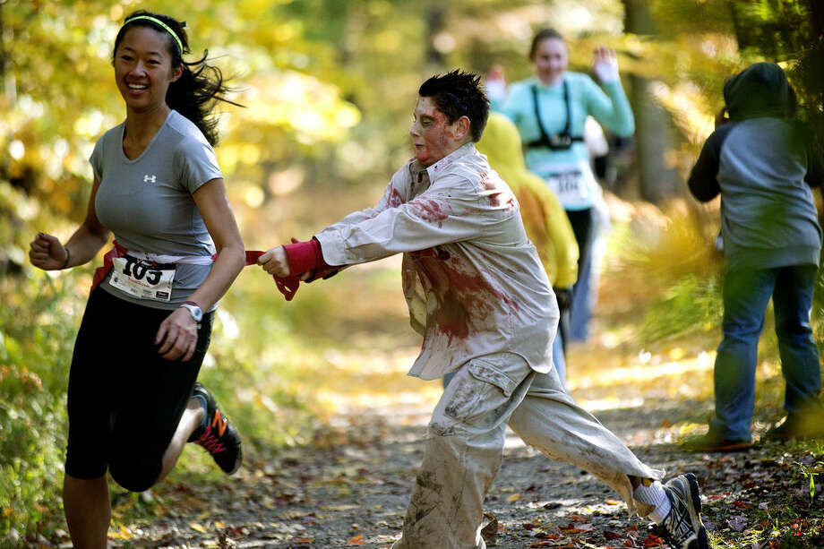 """Zombie Logan Herzberg, 11, right, takes a """"vital organ"""" flag from a racer during the Zombie Run on Saturday at City Forest in Midland. Photo: NICK KING 