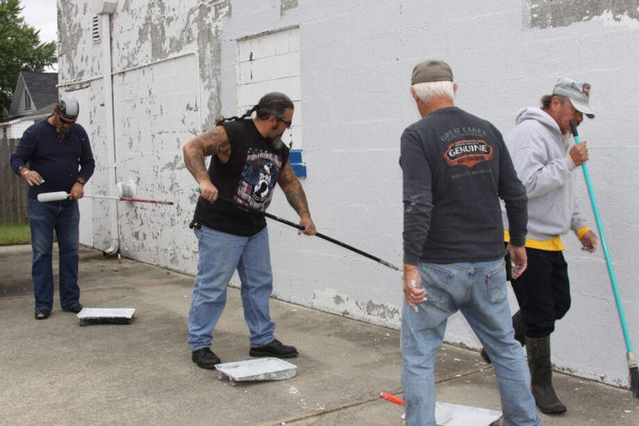 A group of motorcycle enthusiasts paint a building in Midland. Photo: Photo Provided