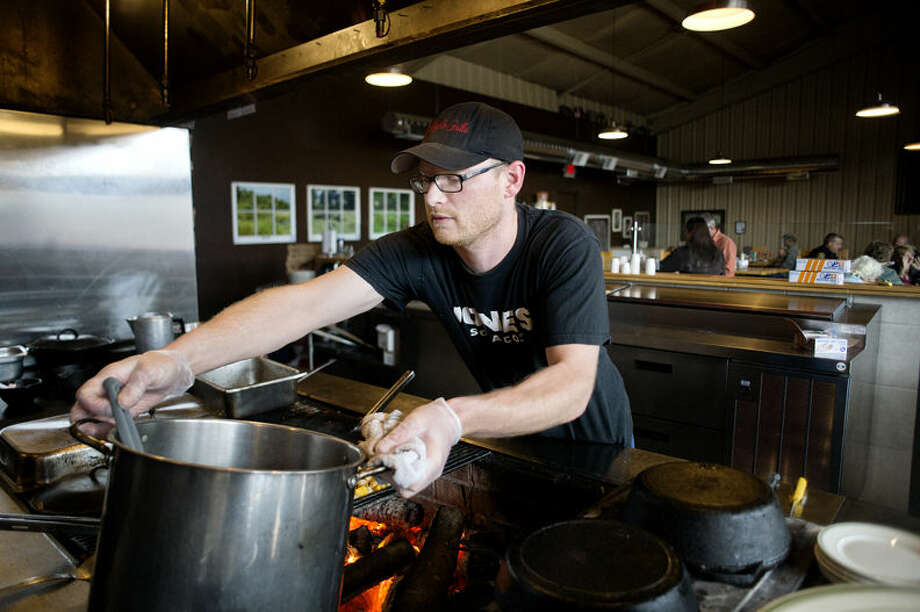 Maple Grille chef Josh Schaeding prepares food at the Hemlock restaurant. Photo: Nick King/Midland  Daily News