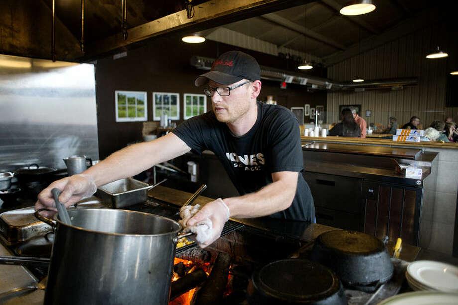 Maple Grille chef Josh Schaeding prepares food at the Hemlock restaurant. Photo: Nick King/Midland  Daily News
