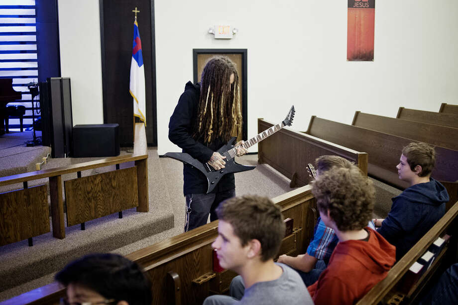 """Brian """"Head"""" Welch, guitarist for the band Korn, plays a quick riff on Adam Newton's guitar after talking with youth about his past struggles with addiction on Friday afternoon at the Midland Nazarene Church. Photo: SEAN PROCTOR 