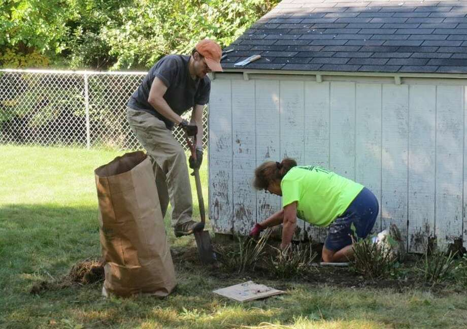 Jamie Spence, left, and Tana Zemanek work in the flower bed around a shed at Paul and Fern Clifford's home in Midland over the weekend. Photo: Annette Clark | Photo Provided