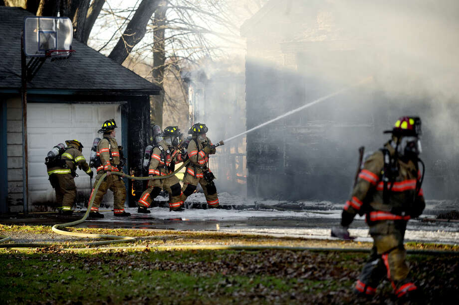 Midland City Firefighters work to extinguish a fire at 1211 Sandow Road, north of M-20 Saturday after 5 p.m. Firefighters reported that the house was fully engulfed when they arrived on the scene. The cause of the blaze is under investigation.