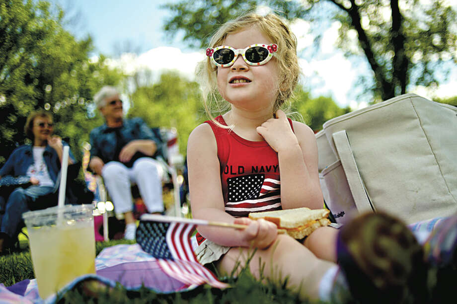 Ava Petroski, 4, of Midland, relaxes on the grass while enjoying a picnic dinner with her mother Christin (not pictured) before the start of the 4th of July celebration on Friday afternoon at Chippewassee Park near the Tridge. Tunes by the Tridge hosted two concerts country acts Butch Heath and Steve Armstrong and the 25 Cent Beer Band. A fireworks show was scheduled at dark. Photo: Nick King/Midland  Daily News / Midland Daily News