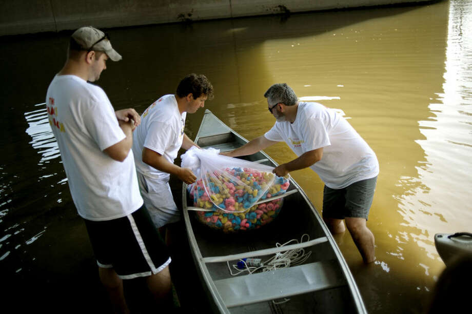 Blain Anderson, center, and Chris Mundhenk, right, unload rubber ducks from a canoe under the M-20 overpass as Scott Little, left, looks on before the start of the Quacktacular Float for Hope duck race on Saturday during RiverDays. Photo: NICK KING | Nking@mdn.net