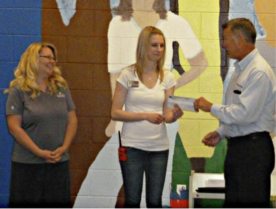 Early Childhood Director Trixie Onstott (left) looks on as Stephanie Varner, 3's classroom teacher, receives a Consumers Energy check from company representative Tom Begin. Photo: Photo Provided
