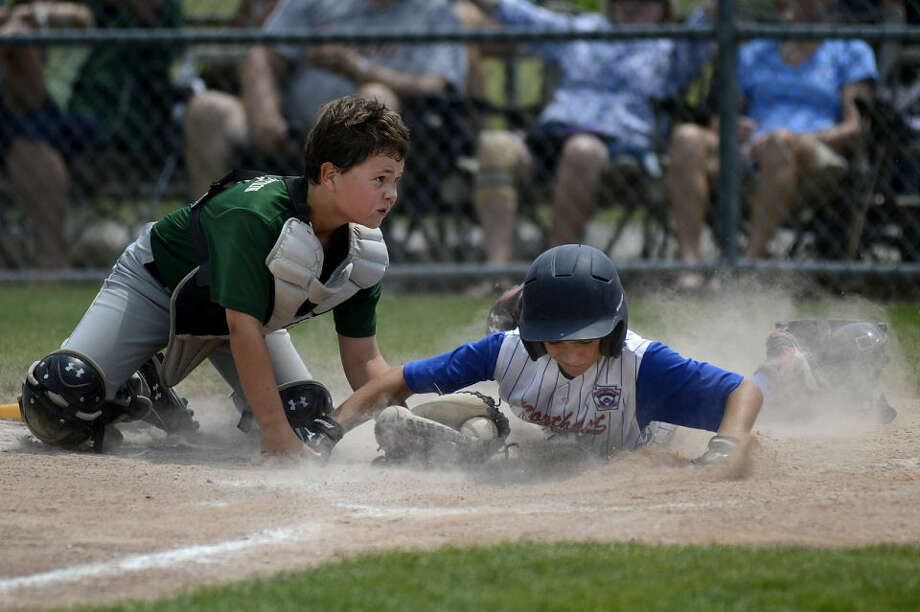 Northeast's Joey Pellitier, right, beats the tag attempt by Freeland's Connor Rump to score in the fifth inning Sunday at Wilson Field. Northeast won 13-3 in five innings. Photo: Nick King | Midland  Daily News