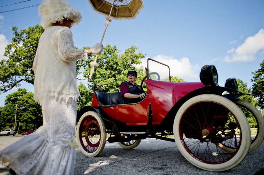 Bill Dreist, right, looks on as his wife, Liz, dressed in vintage attire, gets into the 1914 Saginaw Cycle Car before a ceremonial drive around Hoyt Park. The event was held to celebrate the 100-year anniversary of the car. The car is owned by the Castle Museum of Saginaw County History. Photo: NICK KING | Nking@mdn.net