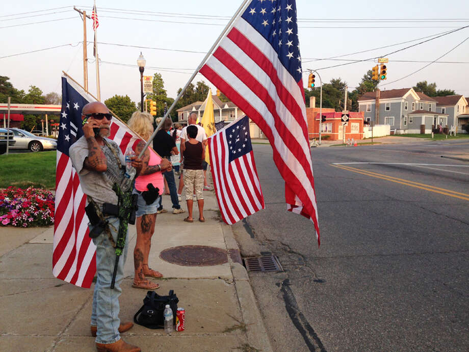 Protesters in Vassar hold American flags and guns outside City Hall as they protest Central American youths possibly coming to a Vassar facility for temporary shelter. Photo: AP Photo | Saginaw News, Lindsay Knake / Saginaw News