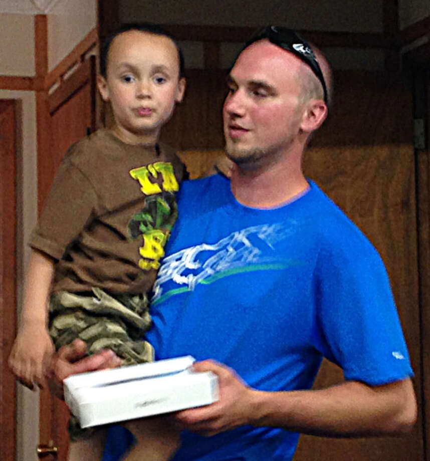 Coleman resident Blake Bower and his 4-year-old autistic son Brayden receive their new iPad from the Coleman Lions Club. Photo: Photo Provided