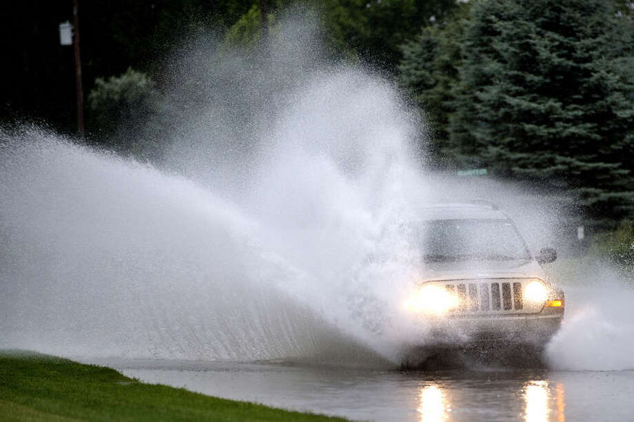 A motorist drives through standing water on East Wackerly Street east of North Jefferson Avenue on Sunday evening after a storm dropped heavy rain in the area. Photo: NICK KING | Nking@mdn.net