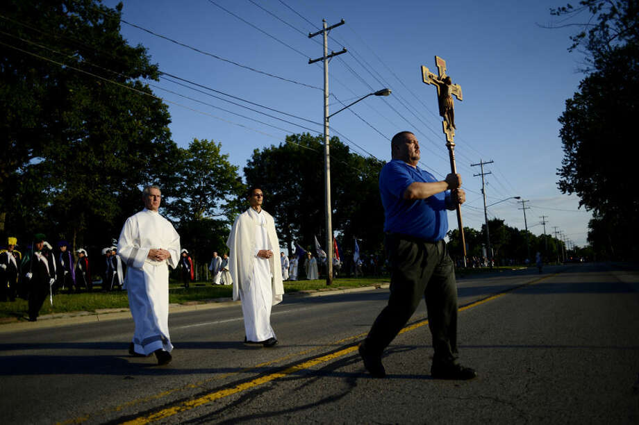Marine Corps veteran Adam Gonzalez, right, carries the crucifix as church members, including seminarian Robert Kelm, left, and altar server Sean Suitor, center, follow on their way back to Holy Family Catholic Church from the Veterans Memorial Plaza on Tuesday in Saginaw. Members of the church, veterans and a group from the Knights of Columbus participated in the ceremony. Saginaw Diocese Bishop Joseph R. Cistone led the Mass before the procession. Photo: NICK KING   Nking@mdn.net