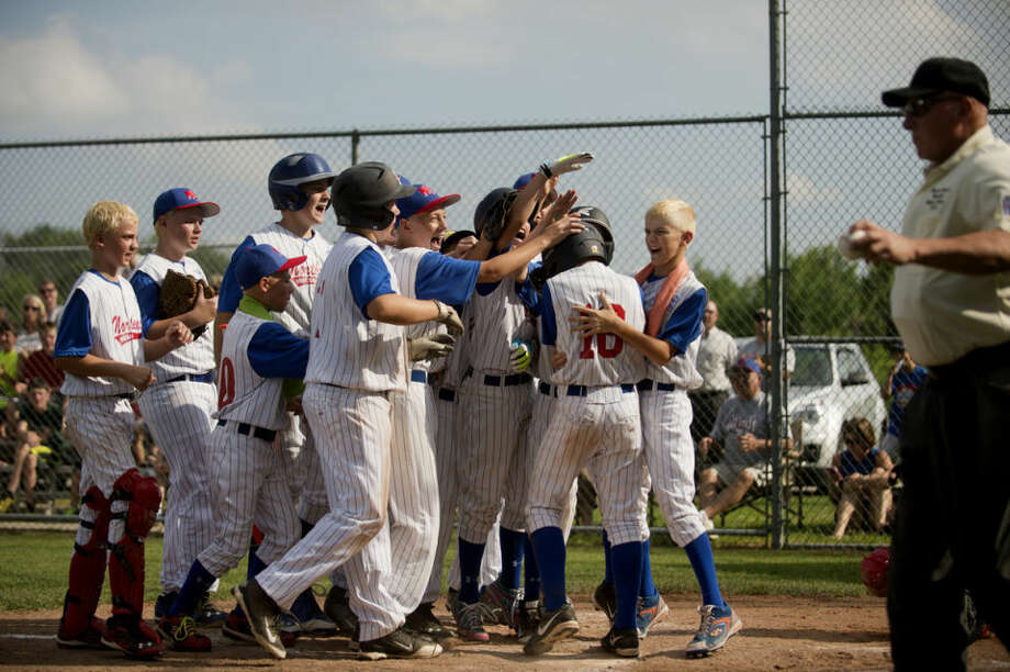 Northeast players surround Matthew Babinski at home plate after he hit a home run in the game against Fraternal Northwest in Midland on Monday. Photo: NEIL BLAKE | Nblake@mdn.net